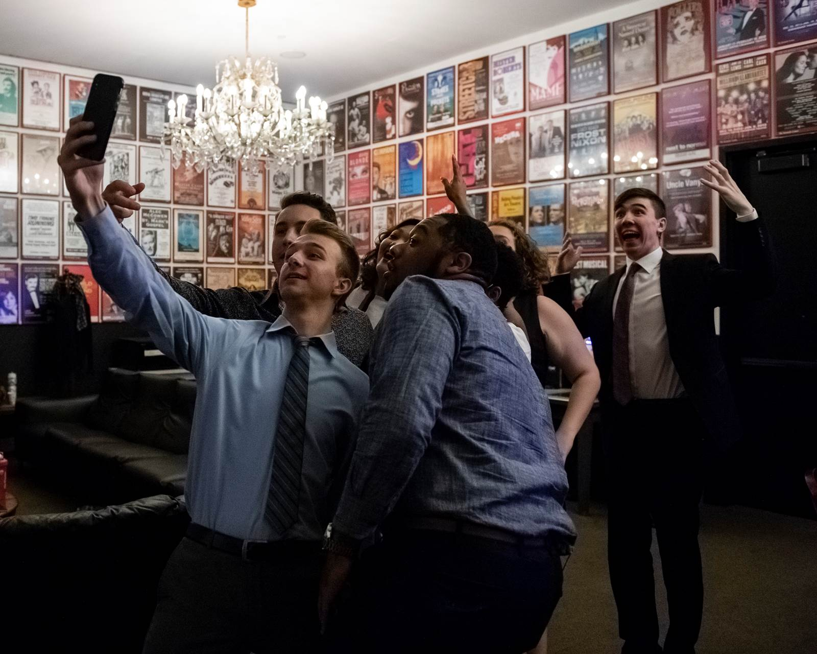 A group of students take a selfie in a room completely lined with show posters.
