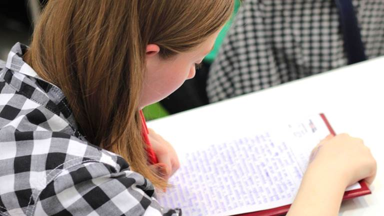 A student looks over their written work