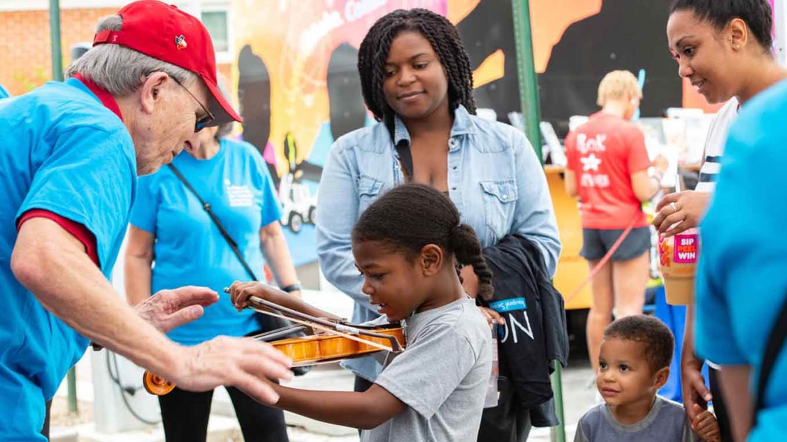 A child learns the violin from an NSO volunteer.